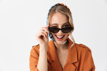 Happy young woman wearing silk stylish scarf posing isolated over white wall background wearing sunglasses winking.