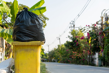 Black garbage placed on the side of the road
