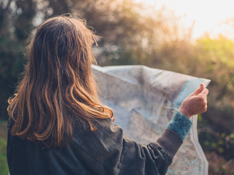 Young hiker woman studying map in nature