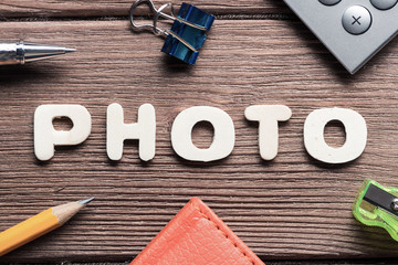 Photo word on wooden table and office stationary around