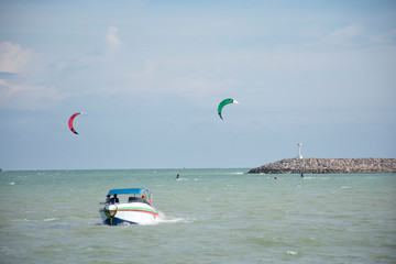 Thai athletes and foreigner people practicing sports and playing kiteboarding or sea kite in the ocean in Rayong, Thailand