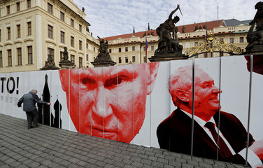 An activist sets up a paper wall depicting Russian President Vladimir Putin and Czech President Milos Zeman during a flash mob event in front of Prague Castle in Prague