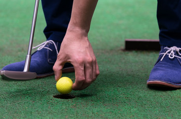 minigolf player pulls a yellow ball out of the hole, close-up