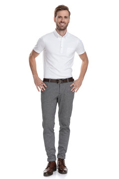 happy young smart casual man with hands on waist