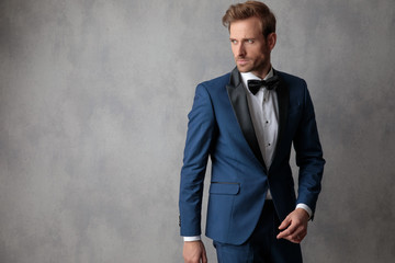 Elegant man stepping to a side while looking at the other side