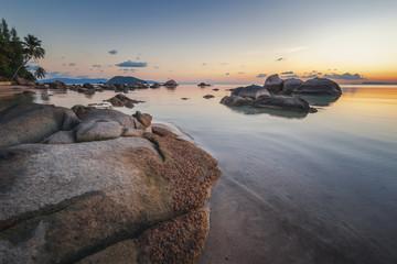 Wall Mural - Sea sunset rocks beach on blue sky background. Beauty evening sunrise. Sandy beach with rocks