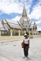 Thai woman standing posing for take photo with Ubosot of Wat Sothon Wararam Worawihan in Chachoengsao, Thailand.