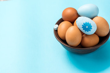 Easter eggs of brown color lie in a dark clay plate on a beautiful blue background. Easter ideas. Space for text. Happy easter.