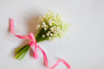 Close-up bouquet of lilies of the valley tied with a pink ribbon on white background. Place for text.