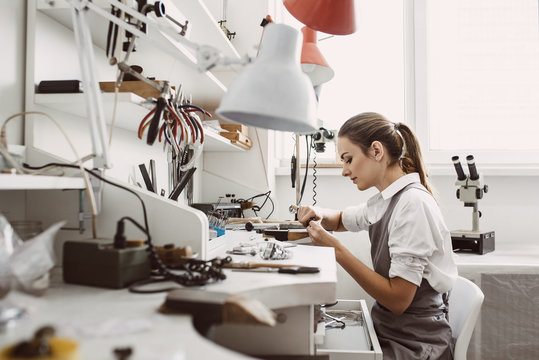 Busy working. Side view of young female jeweler working on a new jewelry product at her workbench. Jewelry making process.