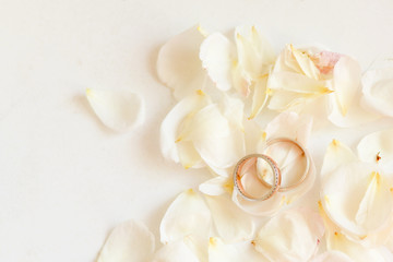 Beautiful toned picture with wedding rings lie on white against the background of flowers