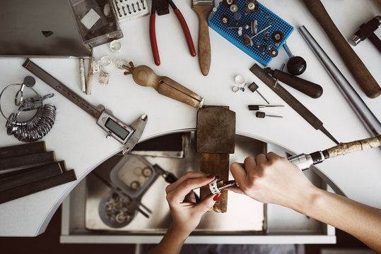 Creative chaos. Top view of jeweler's workbench with different tools for making jewelry. Female jeweler's hands polishing a silver ring