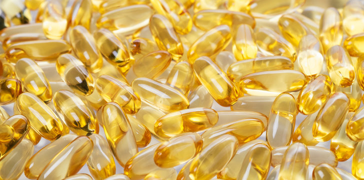 yellow fish oil capsules, omega 3, on white background
