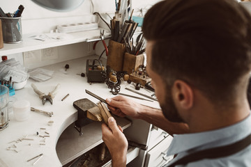 Handmade. Back view of young male jeweler making a ring at his workbench.