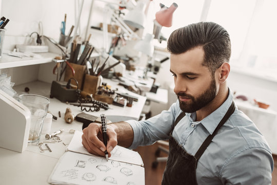 Creative work. Portrait of young bearded jeweler drawing a sketch of a new ring