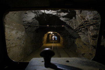 Underground gold ore mine shaft tunnel gallery passage with rails and light