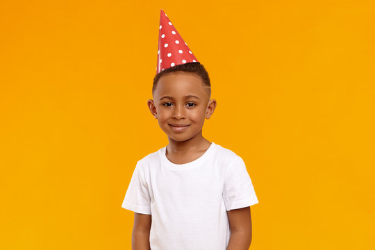 Happy childhood, joy, celebration and holidays concept. Portrait of joyful birthday boy wearing casual t-shirt and red cone hat celebrating ten year old anniversary, looking and smiling camera