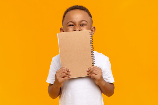 Studio image of overjoyed emotional ten year old dark skinned boy grimacing doesn't want to do homework, holding copybook, covering face. Funny naughty black schoolboy doing home assignment