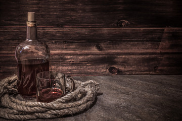 pirates bottle and glass on atone table, old rope, rum oe whiskey in transparent bottle, wooden background