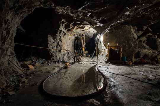 Underground gold ore mine shaft tunnel gallery passage with drilling rig machine