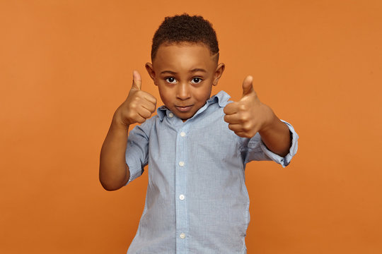 Human reaction, feelings, emotions and body language. Handsome charming African American little boy staring at camera with cool confident look, showing thumbs up gesture as sign of approval