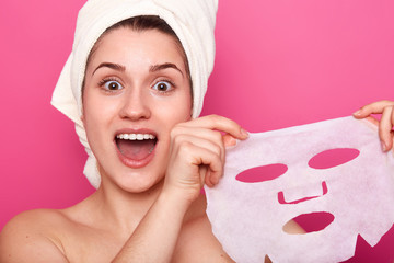 Headshot of amazed beautiful young woman holds cosmetic mask, feels refreshed and energized, has wrapped towel on head, looks with amazement directly at camera, isolated over pink background