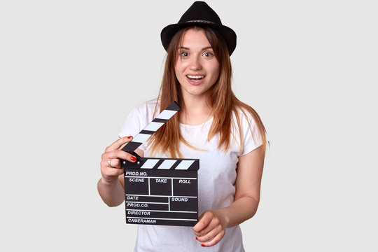 Movie concept. Positive young woman in hedgear holds cinema clapper, dressed in casual t shirt, has pleased expression, isolated over white background. Smiling actress prepares for shooting film
