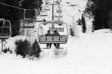 Fototapete - Two skiers on chair-lift in gray day