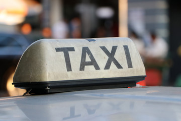 Taxi light sign or cab sign in drab white color and black text on the car roof.