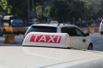Taxi light sign or cab sign in white and red color with white text on the car roof.