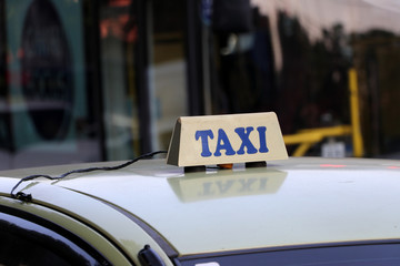 Taxi light sign or cab sign in drab white color with blue text on the car roof.