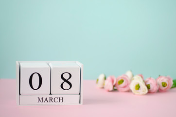 International Womens Day concept. White wooden cubes with 8 th march and flowers on pastel background. Copy space