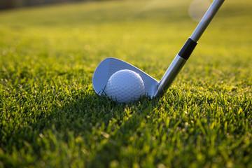 Colocacion de bola y palo de golf atardecer