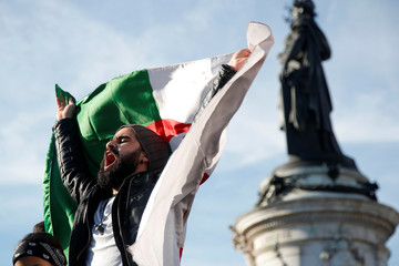 A demonstrator waves an Algerian flag near the  Monument to the Republic during a protest in Paris