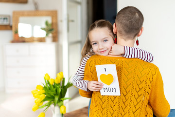 Happy Mother's Day or Birthday Background. Adorable young girl giving her mom, young cancer patient, homemade I LOVE MOM greeting card. Family celebration concept.