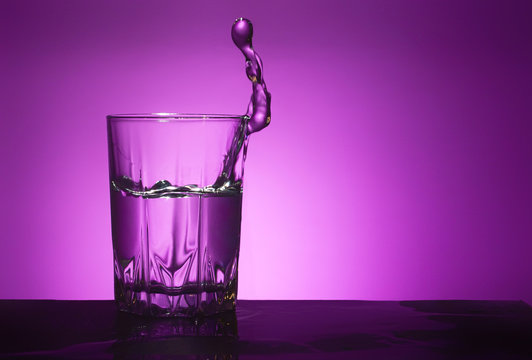 Splash of water in a glass on a purple background