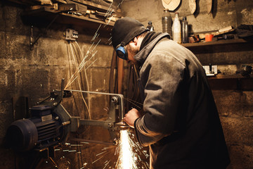 the master grinds the knife on a belt grinder and many sparks are produced.