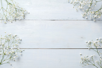 Spring background, flowers frame on blue wooden table. Banner mockup for Womans or Mothers Day, Easter, spring holidays. Flat lay, above view.