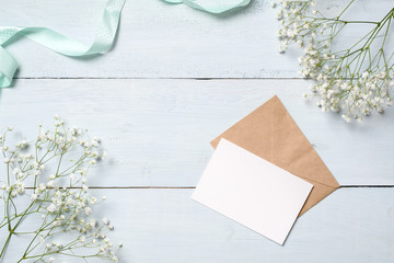 Kraft envelope and blank card on blue wooden desk with flowers. Empty greeting card for your congratulation with Easter, Mother or Womans day, spring background,