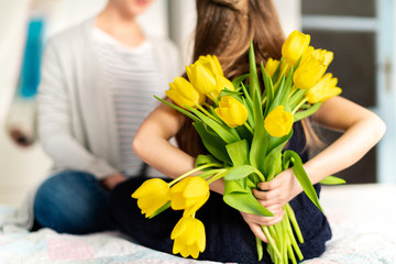 Happy Mother's Day or Birthday Background. Unrecognizable young girl surprising her mom with bouquet of yellow tulips. Family celebration concept.