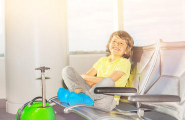 Boy sits in departure terminal waiting for flight