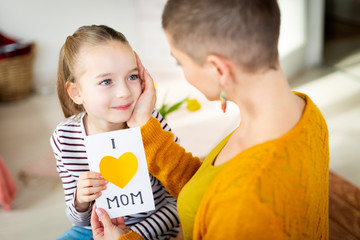 Young female cancer patient thanking her adorable young daughter for homemade I LOVE MOM greeting card. Family celebration concept. Happy Mother's Day or Birthday Background.