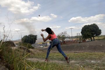 Woman throws a stone towards the Venezuelan side of the border, in Pacaraima