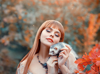 attractive young girl with fiery red straight hair plays with her pet, elf princess plays animal fairy with wild ferret, holds it in her hands on her shoulder. autumn makeup on a lady in the sun.