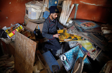 Palestinian worker shows materials and pictures in the remaining part of an abandoned cinema in Tulkarm in the Israeli-occupied West Bank