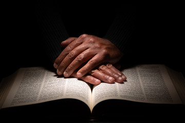 African American Man Praying with Hands on Top of the Bible Wall mural