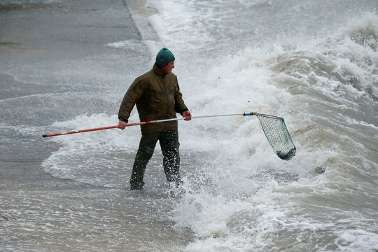 A man uses a net to catch fish which escaped from an offshore fish farm as gale force winds and rough seas lash the Maltese islands, in St Paul's Bay