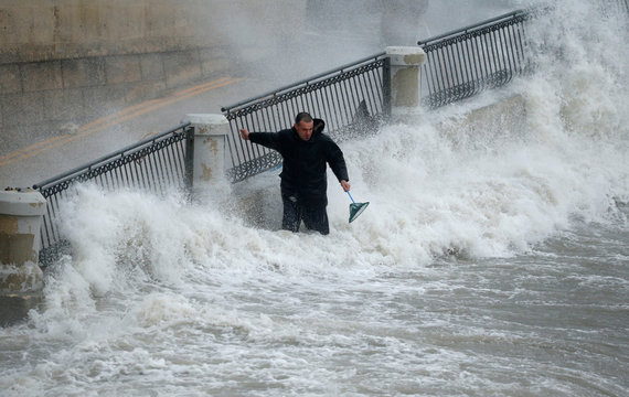 A man holds on to railings while trying to catch fish which escaped from an offshore fish farm as gale force winds and rough seas lash the Maltese islands, in St Paul's Bay