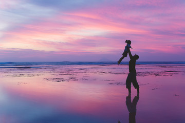 Father lifts his daughter on the beach at dusk