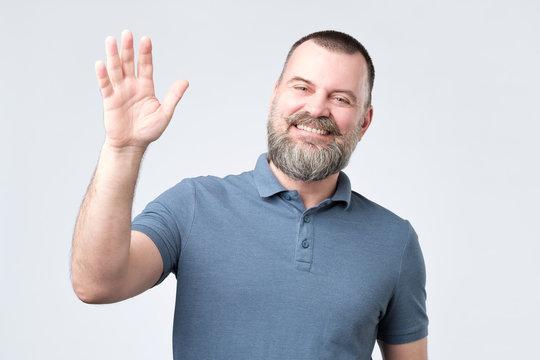 Polite ymature man with beard dressed in denim shirt saying hi, waving with hand